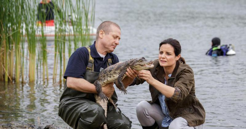 Susanne und ein Helfer haben einen Kaiman im See gefangen.